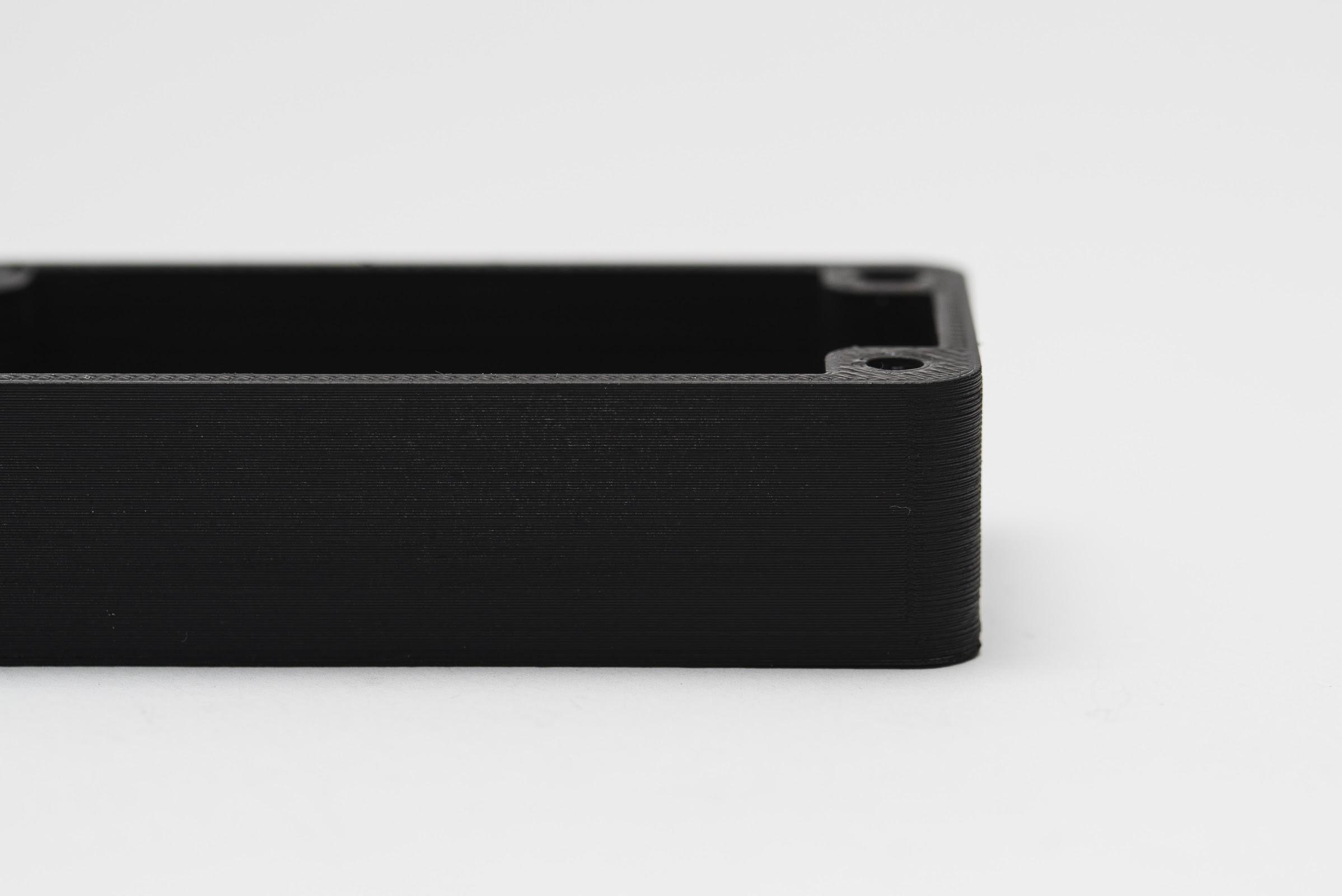 یک قطعه PLA قهوه ای ساخته شده با پرینتر سه بعدی FDM . این قطعه با اسپری رنگ مشکی رنگ شده است.