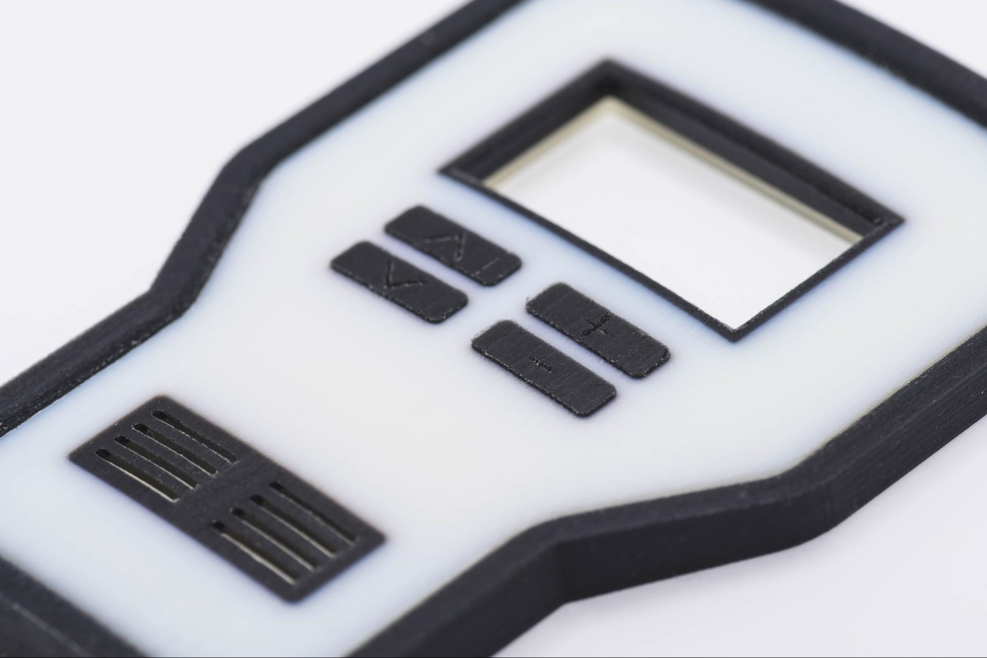 یک نمونه پرینت سه بعدی مولتی متریال تشکیل شده از بخش هاش سفید محکم و مشکی انعطاف پذیر لاستیکی.