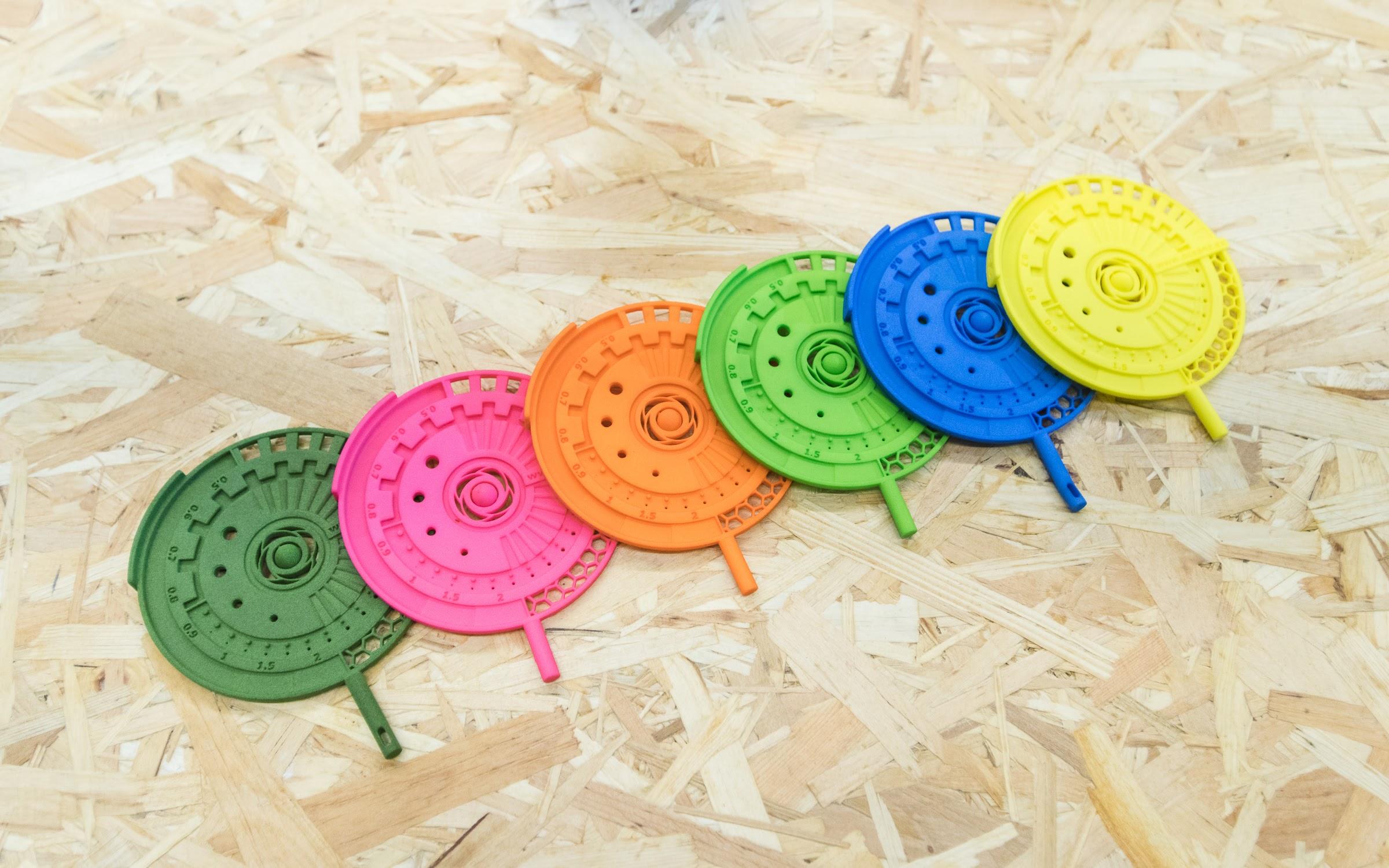 نمونه هایی از قطعات تولید شده با پرینتر سه بعدی SLS که با روش رنگرزی به رنگ های مختلفی درآمده اند.